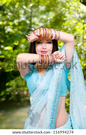 Beautiful young indian woman in traditional clothing with bridal makeup and jewelry. brunette bride traditionally dressed in India. Girl bollywood dancer in Sari. - stock photo