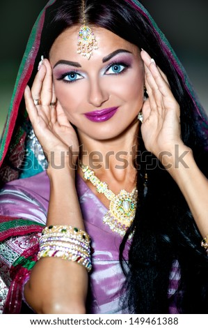 Beautiful young indian woman in traditional clothing with bridal makeup and jewelry. gorgeous brunette bride traditionally dressed in India. Girl bollywood dancer in Sari. and henna on hands - stock photo