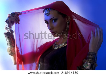 Beautiful young indian woman in traditional clothing with bridal makeup and oriental jewelry. Beautiful Girl bollywood dancer in Sari. Arabian bellydancer (blue lens effect) - stock photo
