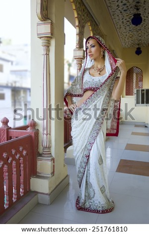 Beautiful young indian woman in traditional clothing with bridal makeup and oriental jewelry. Beautiful Girl bollywood dancer in Sari posing outdoor near the eastern palace  - stock photo