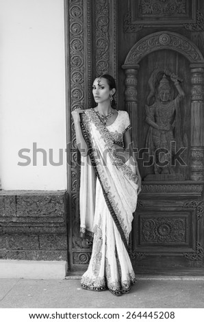 Beautiful young indian woman in traditional clothing with bridal makeup and oriental jewelry. Girl bollywood dancer in Sari posing outdoor near the eastern palace. Eastern fairy tale
