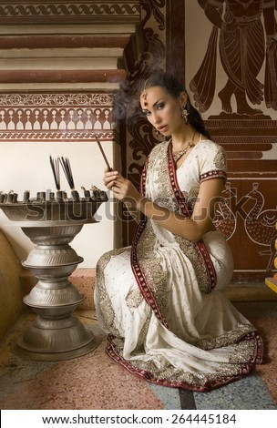 Beautiful young indian woman in traditional clothing with incense bridal makeup and oriental jewelry. Girl bollywood dancer in Sari, eastern palace. Beautiful princess praying. Eastern fairy tale - stock photo