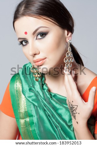 Beautiful young indian woman in traditional clothing with make-up and jewelry. Close-up portrait of a brunette traditionally dressed in sari. Bollywood dancer girl from India. Arabian bellydancer