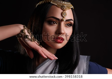 Beautiful young indian woman in traditional clothing with make-up and jewelry. Close-up portrait of a brunette traditionally dressed in blue sari. Bollywood dancer girl from India. Arabian bellydancer - stock photo