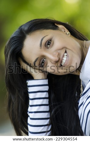 Beautiful young Indian woman smiling and posing - stock photo
