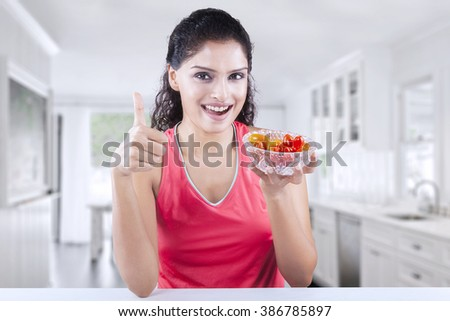 Beautiful young Indian woman smiling at the camera while holding a bowl of fresh strawberry and showing thumb up at home