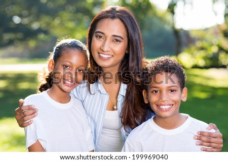 beautiful young indian woman with her children outdoors - stock photo