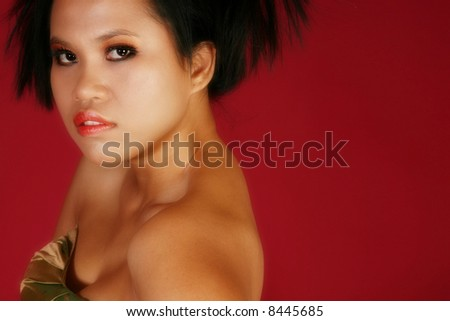 Beautiful young Indonesian woman in formal over red. - stock photo