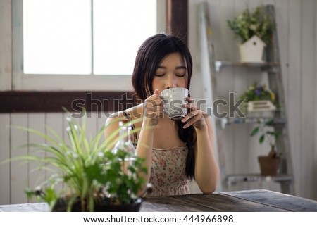 Beautiful Young Japanese Woman is drinking coffee at home - stock photo