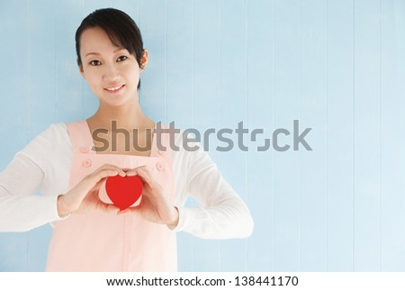 Beautiful young japanese woman to make a heart, blue tiled background with copy space. - stock photo