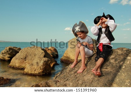 Beautiful young kids pirate boy and girl holding a pirate map and a magnifying glass looking for buried treasure on the beach - stock photo