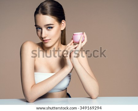 Beautiful young lady applying moisturizing creme, skin care concept / photo of attractive brunette girl on beige background - stock photo