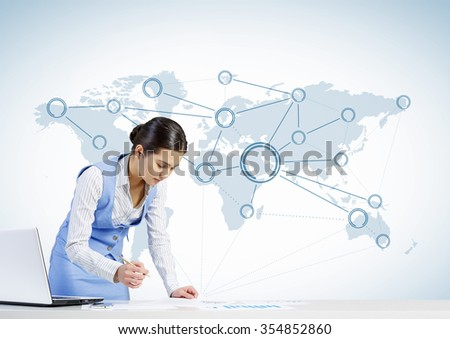 Beautiful young lady at desk working on laptop with social network concept