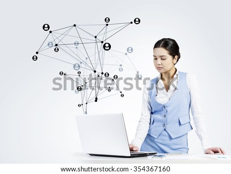 Beautiful young lady at desk working on laptop with social network concept at background