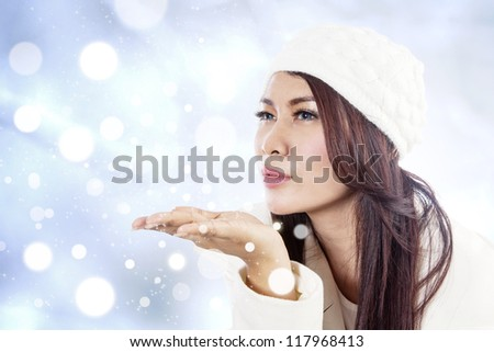 Beautiful young lady blowing snowflakes on blue unfocused lights background