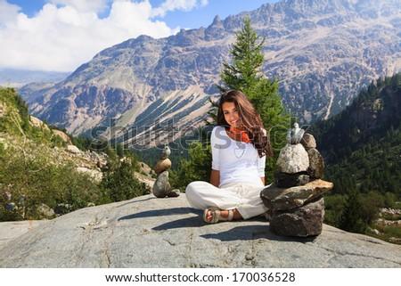 Beautiful young lady enjoying the beauty of the Swiss mountains. - stock photo