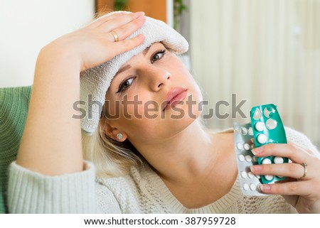 Beautiful young lady having a migraine. She is sittin on a couch at home with a wet towel on her forehead and painkillers in her hands - stock photo