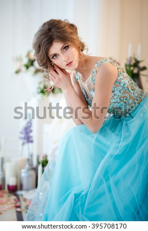 Beautiful young lady in a luxury blue dress in elegant interior decorated with flowers