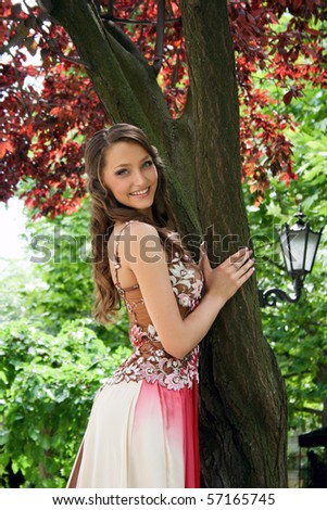 Beautiful young lady in the park near the tree