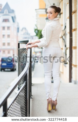Beautiful young lady in white pants and jacket posing outdoors - stock photo