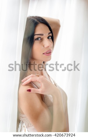 Beautiful young lady looking at the window. Closeup portrait - stock photo