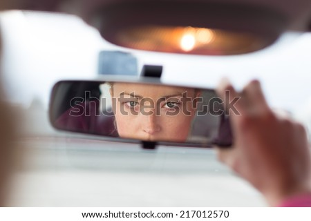 Beautiful young lady looking back through the rear view mirror from the front seat of a car while reversing. - stock photo