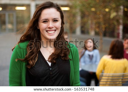 Beautiful young lady outside with friends - stock photo