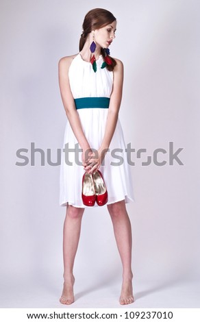 Beautiful young lady posing in white dress with bright accessories - stock photo