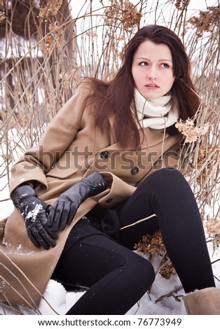 Beautiful young lady posing sitting on snow in brown coat
