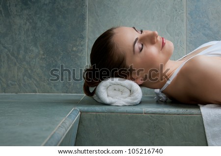 Beautiful young lady relaxing in a turkish bath at spa club - stock photo