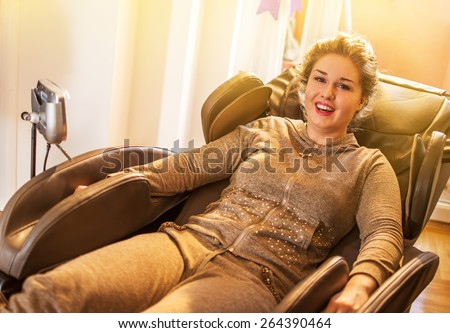 Beautiful young lady relaxing in the massage chair while the sunset. - stock photo