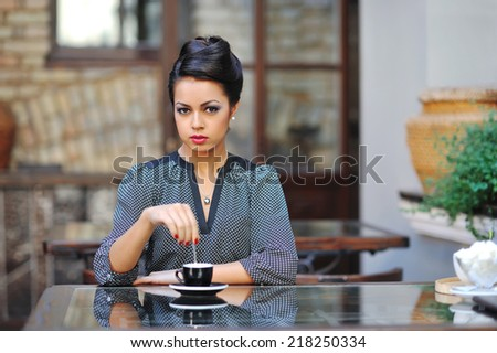Beautiful young lady sitting in the cafe for a cup of coffee - stock photo