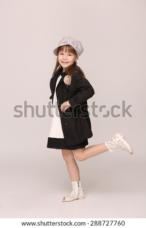 Beautiful young lady smiling for photo camera. Girl in black coat and white shoes in studio. - stock photo