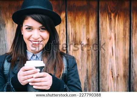 Beautiful young lady smiling while enjoying her warm coffee,selective focus - stock photo