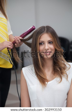 Beautiful young lady straightener her hair at the hairdresser salon. - stock photo