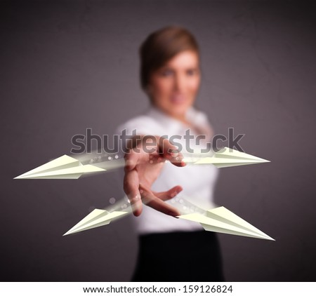 Beautiful young lady throwing origami airplanes - stock photo