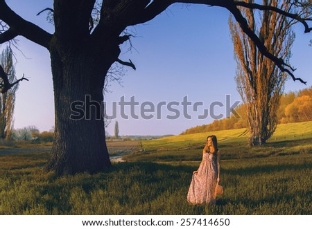 Beautiful young lady walking in nature on sunny spring day. - stock photo