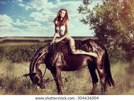 Beautiful young lady wearing in sexy lingerie riding a horse at sunny summer day. Vintage and toned photo.