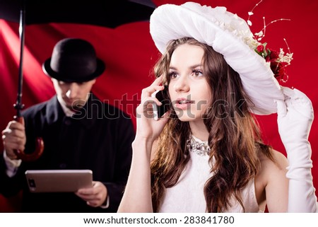 Beautiful young lady wearing white hat and talking on mobile phone over male with umbrella and tablet pc computer - stock photo
