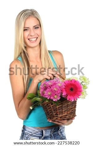 Beautiful young lady with a basket of colorful flowers - stock photo
