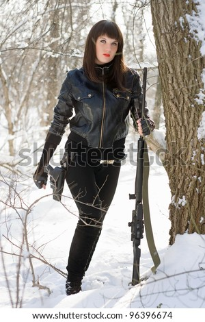 Beautiful young lady with a sniper rifle - stock photo