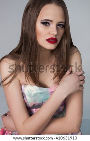 Beautiful young lady with big red lips. Girl with Luxury and provocative Makeup isolated on gray background in studio. Fashion Beauty close up. Gorgeous portrait. - stock photo