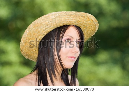 Beautiful young lady with hat over green background - stock photo