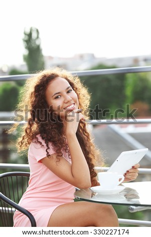 Beautiful young lady with tablet sitting at the summer terrace