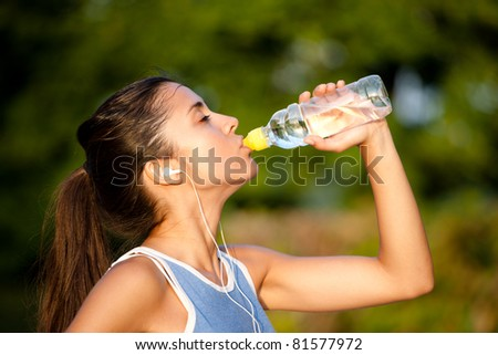 Beautiful young latin woman drinking water after training - stock photo