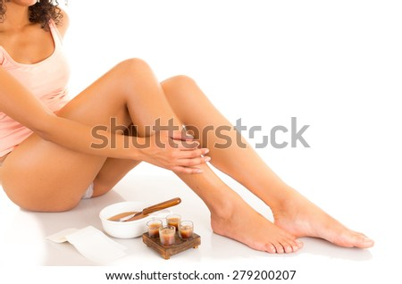 Beautiful young latin woman with silky skin caressing her legs, concept of leg waxing, isolated on white