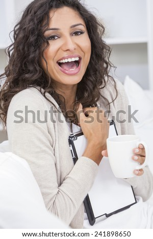 Beautiful young Latina Hispanic woman smiling, laughing, relaxing and drinking a cup of coffee or tea using tablet computer - stock photo