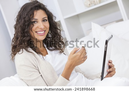 Beautiful young Latina Hispanic woman smiling, relaxing and drinking a cup of coffee or tea using tablet computer - stock photo