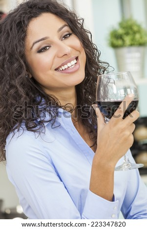 Beautiful young Latina Hispanic woman smiling, relaxing and drinking a glass of red wine - stock photo