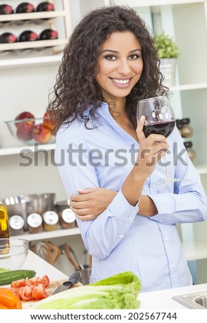 Beautiful young Latina Hispanic woman smiling, relaxing and drinking a glass of red wine in her kitchen at home while preparing a healthy salad - stock photo